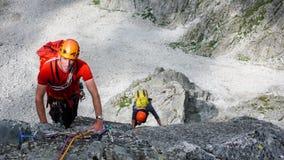 Twee mannelijke rotsklimmers op een graniet die route in de hoge alpiene pieken van zuidoostelijk Zwitserland beklimmen royalty-vrije stock foto