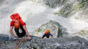 Twee mannelijke rotsklimmers op een graniet die route in de hoge alpiene pieken van zuidoostelijk Zwitserland beklimmen royalty-vrije stock afbeelding