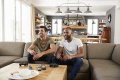Twee Mannelijke Sporten van Vriendensit on sofa and watch op Televisie royalty-vrije stock afbeelding