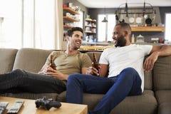 Twee Mannelijke Sporten van Vriendensit on sofa and watch op Televisie royalty-vrije stock foto