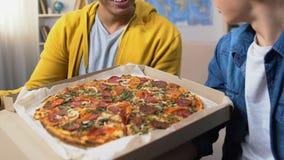 Twee mannelijke studenten die pizzadoos openen en smakelijk bekijken caloried maaltijd, fastfood stock videobeelden