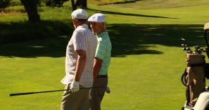 Twee mannelijke vrienden die en op de golfcursus babbelen lopen voorbij hun kart stock footage