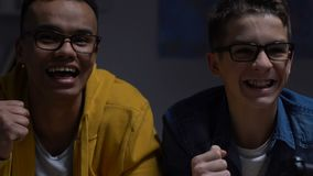 Twee mannelijke vrienden die het winnen in videospelletje vieren, weekendnacht sleepover stock video