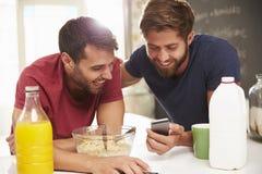Twee Mannelijke Vrienden die Ontbijt hebben en Tekstbericht lezen Royalty-vrije Stock Foto