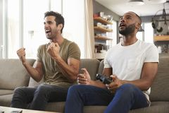 Twee Mannelijke Vrienden die op Sofa In Lounge Playing Video-Spel zitten Stock Fotografie