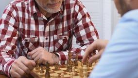 Twee mannelijke vrienden die schaak spelen, die over strategie, gemeenschappelijke hobby, close-up denken stock videobeelden