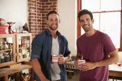 Twee mannelijke vrienden die uit in keuken hangen die aan camera kijken royalty-vrije stock foto's