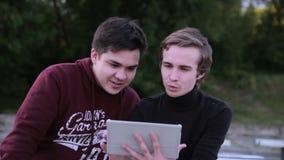 Twee mannelijke vrienden met tabletcomputer spreken die in openlucht surfen stock videobeelden