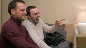 Twee mannelijke vrienden op bank het letten op televisie en het lachen Stock Foto