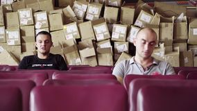 Twee mannelijke vrienden zitten in rij van purpere stoelen met lege dozen achter hun ruggen stock video