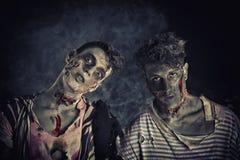 Twee mannelijke zombieën die zich op zwarte rokerige achtergrond bevinden Royalty-vrije Stock Foto
