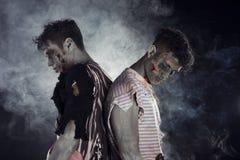 Twee mannelijke zombieën rijtjes op zwarte rokerige achtergrond Stock Foto's