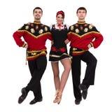 Twee mannen en één vrouw die het volks Russische kostuum stellen dragen Stock Afbeeldingen