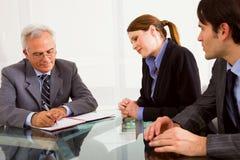Twee mannen en één vrouw tijdens een baangesprek Stock Afbeeldingen