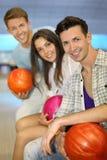 Twee mannen en de vrouw houden ballen in kegelenclub Royalty-vrije Stock Foto's