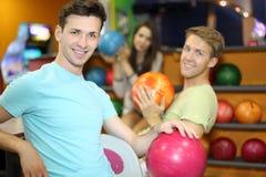 Twee mannen en de vrouw zitten dichtbij planken met ballen Royalty-vrije Stock Foto