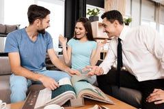 Twee mannen en een vrouw bespreken de aankoop van nieuw meubilair Stock Foto's