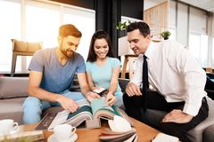 Twee mannen en een vrouw bespreken de aankoop van nieuw meubilair Royalty-vrije Stock Foto