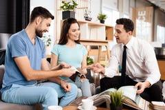 Twee mannen en een vrouw bespreken de aankoop van nieuw meubilair Stock Afbeeldingen