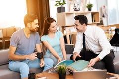 Twee mannen en een vrouw bespreken de aankoop van nieuw meubilair Royalty-vrije Stock Fotografie