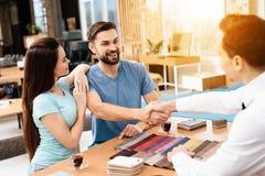 Twee mannen en een vrouw bespreken de aankoop van nieuw meubilair Royalty-vrije Stock Foto's