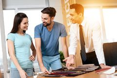 Twee mannen en een vrouw die zich over de stofferingssteekproeven bevinden voor meubilair Stock Foto's