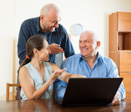 Twee mannen en vrouw bij laptop Royalty-vrije Stock Afbeelding