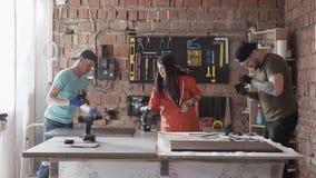 Twee mannen en vrouw die in comfortabele kleren en kappen werken die meubilair in de workshop maken Het moderne mensen maken stock footage