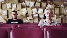 Twee mannetjes zitten in rij van purpere stoelen met stapel van dozen achter hun ruggen stock footage