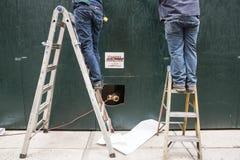 Twee manusjes van alles op ladders Stock Foto