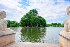 Twee marmeren sfinxkanten en eiland met bomen op de vijver Royalty-vrije Stock Foto's