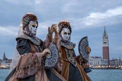 Twee maskeerden vrouwen in kostuum met ventilators, bij het eiland van San Giorgio, met St Tekens erachter Vierkant en klokketore stock foto's