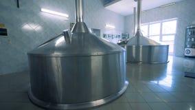 Twee massieve die bussen in een zaal van een brouwerijfabriek worden geplaatst stock video