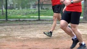Twee mededingers die over hindernissen springen stock footage