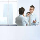 Twee medewerkers die in bureau babbelen Stock Afbeeldingen