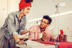 Twee medewerkers die over hun gemeenschappelijk project debatteren stock foto