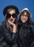Twee meisje het stellen in fotolaars Stock Foto's