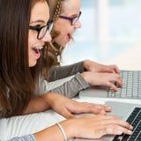 Twee meisje het typen op laptops Stock Afbeeldingen
