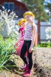 Twee meisje het werken in de tuin het water geven eerste lente bloeit op een zonnige warme dag Stock Afbeeldingen