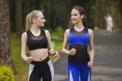 Twee meisjebespreking terwijl het Aanstoten Royalty-vrije Stock Foto's