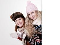 Twee meisjes achter een duidelijke witte raad stock foto