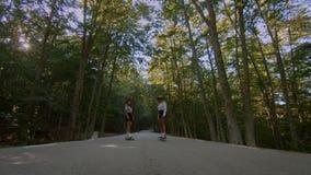 Twee meisjes berijden skateboard longboard op weg stock video