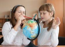 Twee meisjes bestuderen aardrijkskunde gebruikend bol Royalty-vrije Stock Afbeelding
