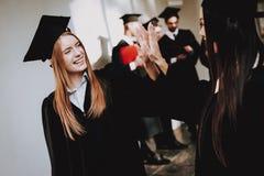 Twee meisjes bevinden zich in de gang van de universiteit in thei royalty-vrije stock afbeeldingen