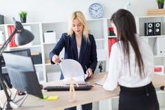 Twee meisjes bevinden zich in het bureau dat over dichtbij de lijst en het werk met documenten wordt gebogen royalty-vrije stock afbeeldingen