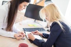 Twee meisjes bevinden zich in het bureau dat over dichtbij de lijst en het werk met documenten wordt gebogen royalty-vrije stock afbeelding