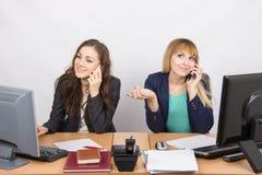 Twee meisjes bij een bureau die op mobiele telefoon in het bureau spreken Stock Foto
