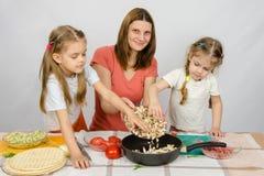 Twee meisjes bij keuken dienen met een ijver in om haar moeder te helpen de paddestoelen van de plaat aan de pan gieten royalty-vrije stock fotografie