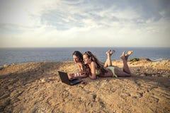 Twee meisjes bij strand het babbelen Royalty-vrije Stock Afbeeldingen