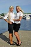 Twee meisjes blonde tribune op de pijler Stock Foto